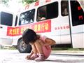体检之余蹲在地上玩耍的小学生
