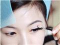 用海绵棒沾取粉色眼影涂在上眼皮