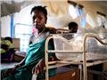 一名刚刚经历了流产的女孩在医院的病床边。