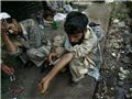 几名吸毒者蹲在肮脏的地方为自己注射海洛因。