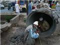 吸毒者躲在街道边的水泥管里吸食海洛因。