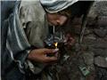 一名毒品吸食者在大力吸食海洛因。多数吸食者都通过偷盗的方式筹集买毒品的钱。