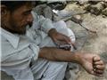 一名男子蹲在小巷里用针管注射海洛因。