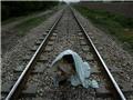一名吸毒者披着床单蹲在铁路中间用银质叶片形容器吸食着海洛因。